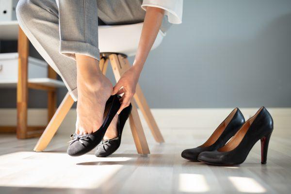 Frau mit Fußschmerzen durch enge Schuhe
