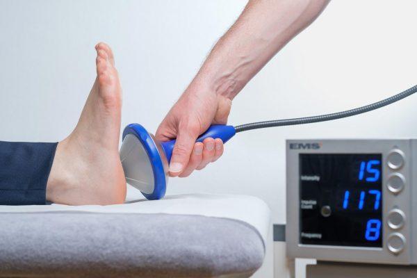 Ein Fuß wird mit Stoßwellentherapie behandelt